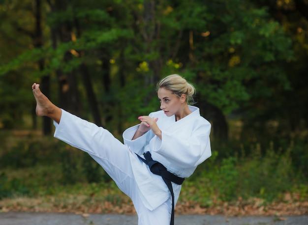 Привлекательная женщина-боец в белом кимоно с черным поясом пинает на улице