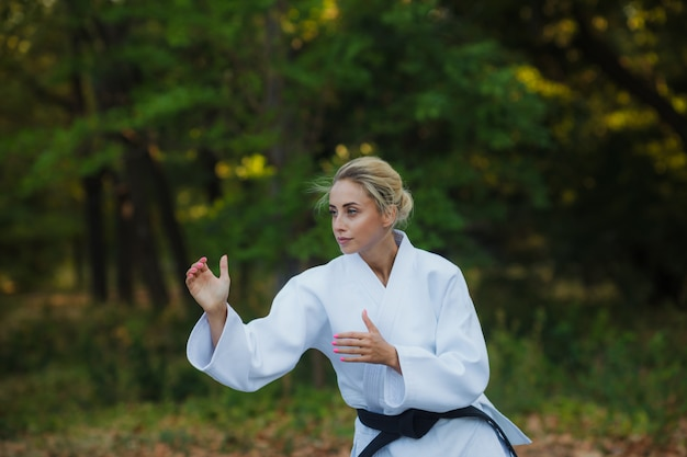 Attractive female master fighter in a white kimono with a black belt stands in a fighting stance outdoors