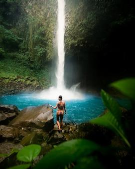 森の中の美しい滝の近くの岩の上に立っているビキニで魅力的な女性モデル
