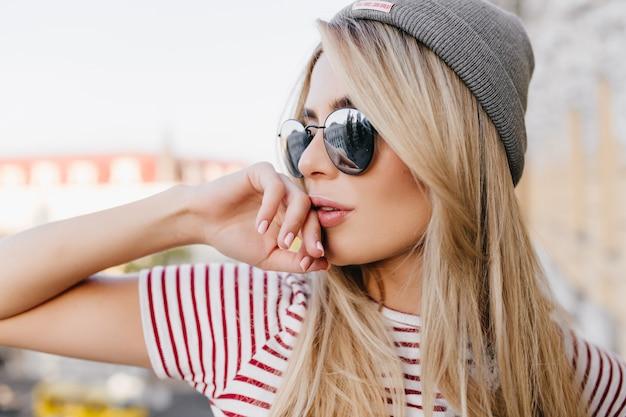 손으로 입술을 만지고 멀리 부드럽게 웃는 회색 모자에 매력적인 여성 모델