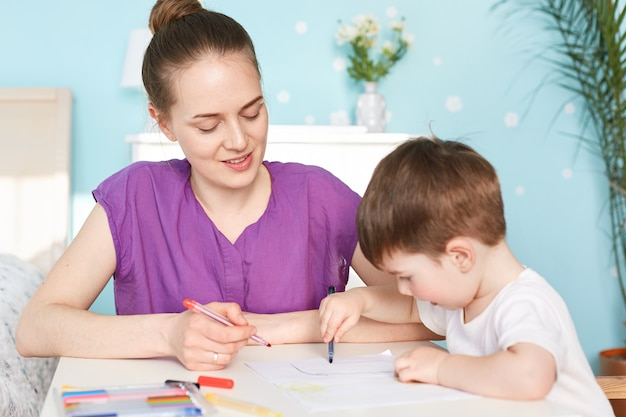Attractive female mother sits near her little son who draws picture on blank piece of paper