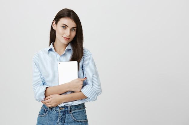 Impiegato di ufficio femminile attraente che tiene compressa digitale e sorridente