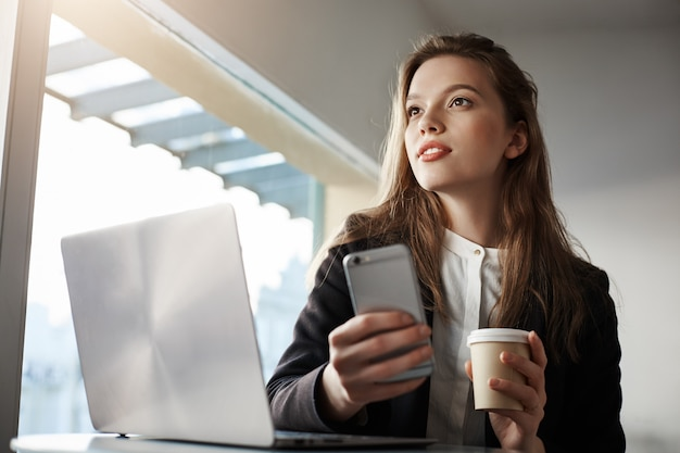 Attractive female office worker, sitting in cafe with laptop, drinking coffee and holding smartphone, dreaming while looking aside