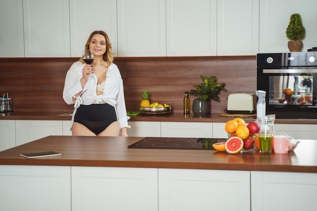 キッチンで下着姿で怠惰な一日を楽しんでいる魅力的な女性