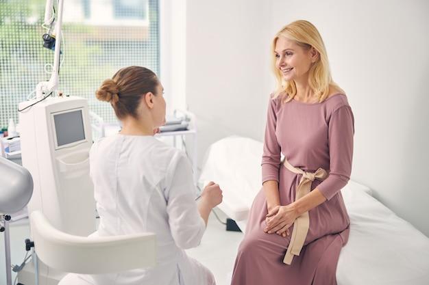 Привлекательная женщина, выражающая позитивный настрой во время консультации с врачом, в данный момент чувствуя себя счастливой
