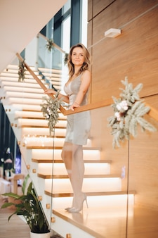 Attractive female person standing on stairs while looking straight at camera. christmas concept