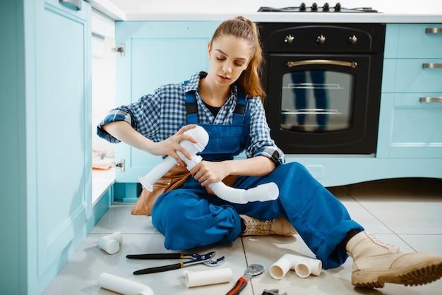 부엌에서 배수 파이프와 균일 한 고정 문제에 매력적인 여성 배관공. 도구 가방 수리 싱크가있는 handywoman, 가정에서의 위생 장비 서비스