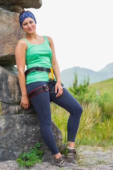 Attractive female rock climber leaning on rock face smiling