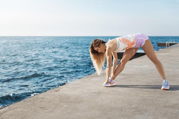 海の近くに立って走る前に毎日朝のトレーニングストレッチをしている魅力的な女性ランナー