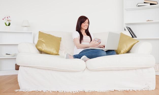 ソファに座っている魅力的な女性は、インターネットで支払いをするつもりです