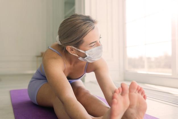 흰색 의료 마스크를 쓰고 매력적인 여성 스포츠 피트니스 코치는 집에서 요가 매트에 운동을합니다.