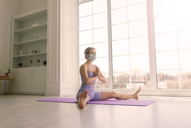 Attractive female sport fitness coach wearing white medical mask do exercises on yoga mat at a home.