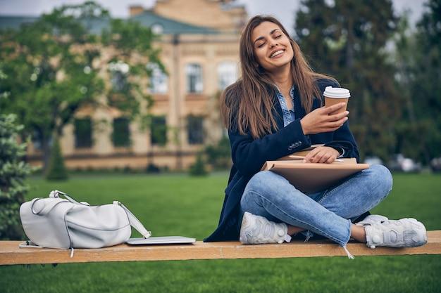 캐주얼 드레스에 벤치에 앉아 음료와 함께 봄 날씨를 즐기는 매력적인 여성 학생