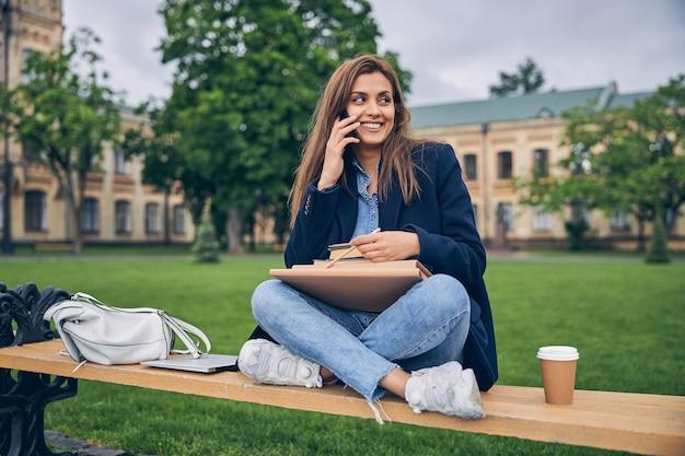 전화로 이야기하고 웃고있는 동안 책과 커피와 함께 벤치에 앉아 매력적인 여성 학생