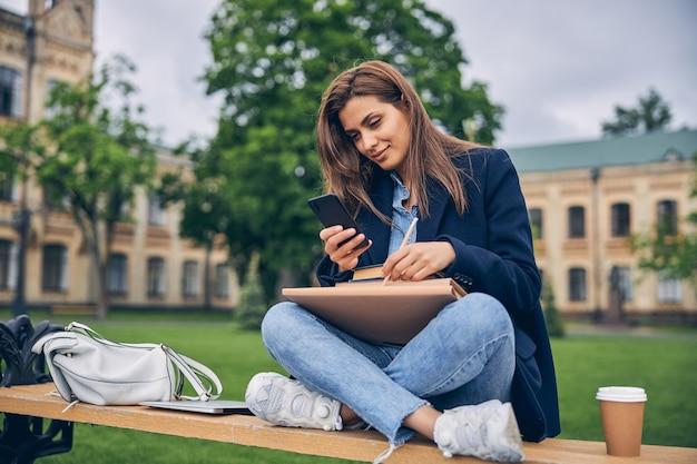 모바일에서 뭔가를 확인하는 동안 커피와 책 벤치에 앉아 매력적인 여성 학생