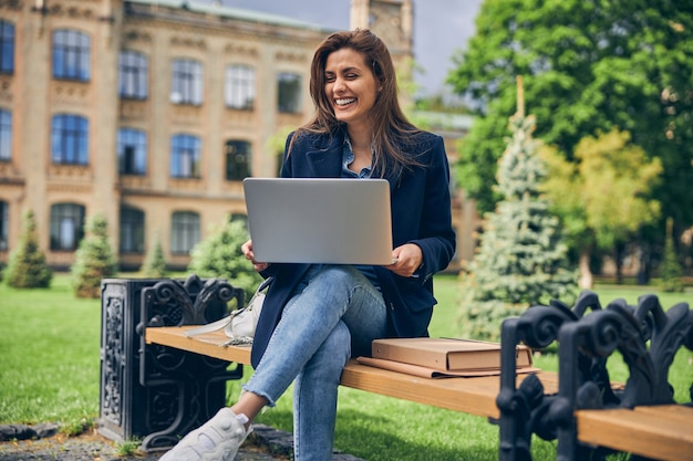 앉아서 컴퓨터에서 작업하고 웃고있는 동안 외부에서 혼자 시간을 보내는 매력적인 여성 학생