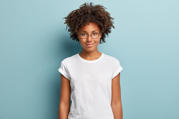 Attractive female student with curly hair, wears transparent glasses, white t shirt, stands against blue background, has calm face expression, tender smile,