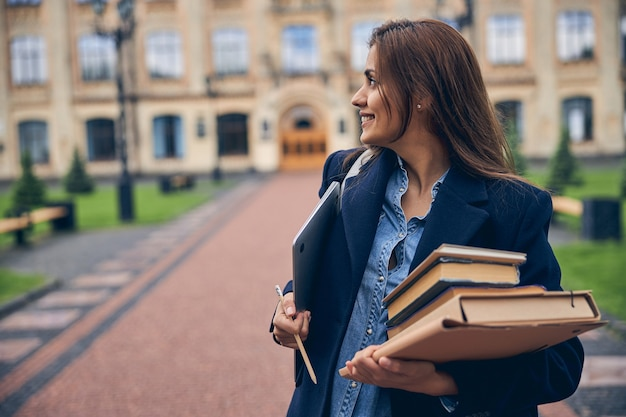혼자 대학 근처에 서있는 동안 웃 고 책과 노트북의 더미와 함께 매력적인 여성 학생