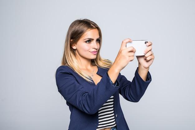 매력적인 여성이 그녀의 휴대 전화로 사진을 찍습니다.