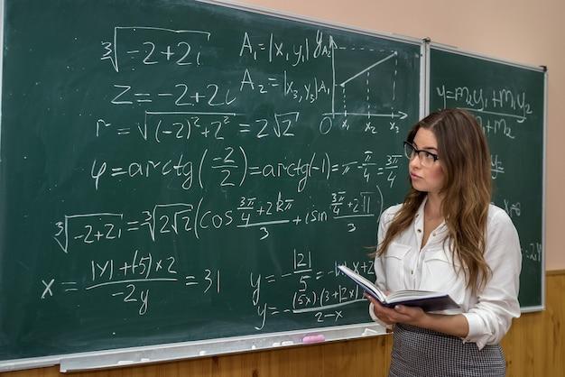 Привлекательная учительница в очках возле доски с математическими расчетами. обратно в школу