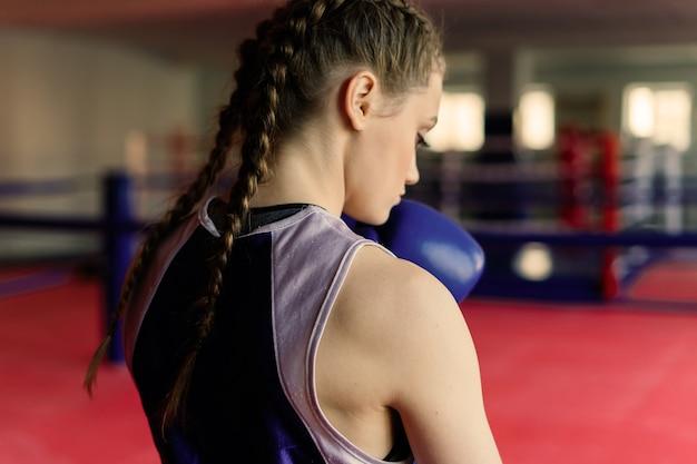 魅力的な女性のトレーニング、ボクシンググローブでバッグをパンチ