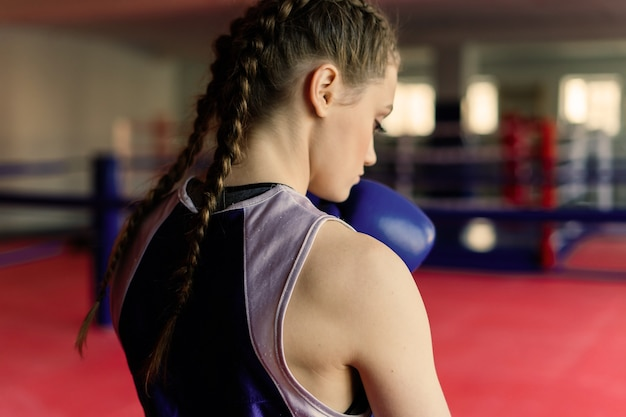 Attractive female training, punching a bag with boxing gloves on