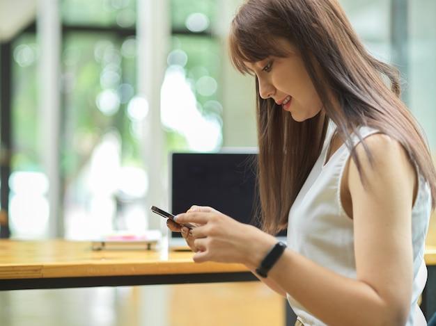 백그라운드에서 웃고 흐릿한 사무실 인테리어와 함께 스마트폰을 사용하는 매력적인 여성