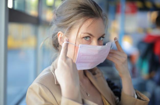 屋内でフェイスマスクを着用した魅力的な女性