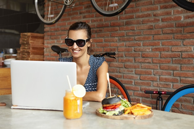 Attractive female wearing shades sitting in front of open generic laptop, looking at screen with happy expression while having video call with friend