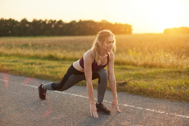 Attractive female wearing sport shoes and clothes, doing sport exercises on road against sunset, liking gymnastics, stretching her legs. active young girl going in for sport, having healthy lifestyle