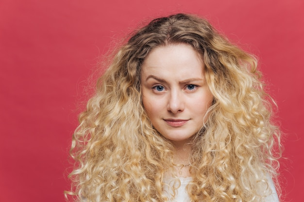 Attractive female with bushy light curly hair, raises her eyebrow