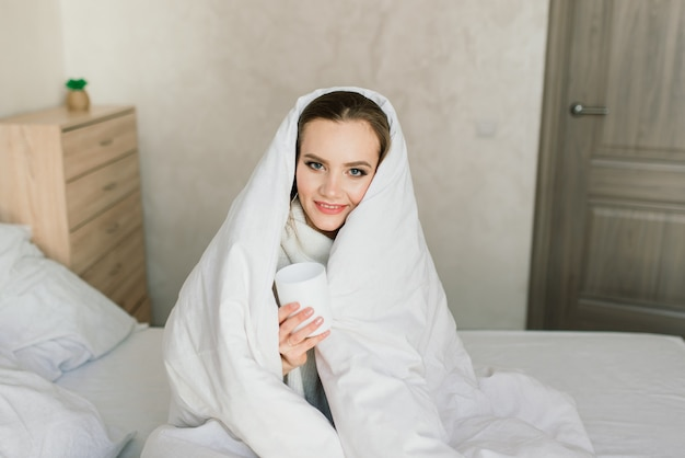 Attractive female with cup of coffee, smartphone and cakes in the bed