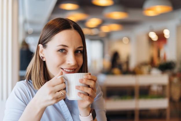 Привлекательная женщина с милой улыбкой за чашкой кофе, расслабляясь в перерыве