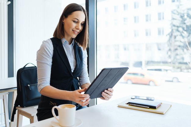 Attractive female with cute smile having a coffee while relaxin in a break with a digital tablet