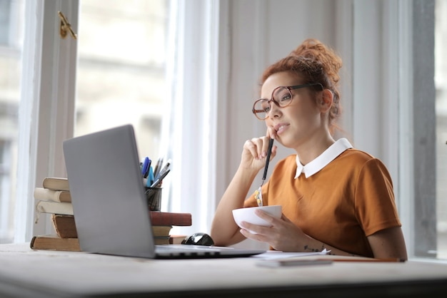 Attractive female with glasses holding a bowl of cereal and sitting in front of a laptop on the desk