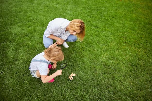 녹색 잔디에 고립 된 자연의 세부 사항을보기 위해 돋보기를 사용하는 그녀의 딸과 함께 매력적인 여성