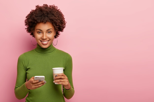 Привлекательная женщина с довольным выражением лица, держит мобильный телефон и кофе с собой, одетая в зеленую одежду, отправляет текстовое сообщение, общается в чате онлайн, изолирована на розовой стене