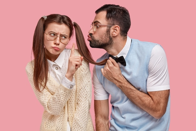 La donna attraente con due code di cavallo rifiuta il bacio del fidanzato, mostra il gesto di fermarsi, indossa grandi occhiali, non vuole iniziare una nuova relazione. i nerd della scuola posano sul muro rosa durante la data