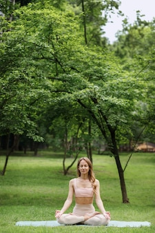 公園で魅力的な女性のヨガインストラクターが瞑想します