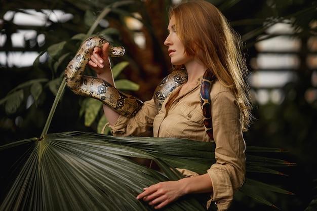 열대 자연에서 파이썬 뱀과 함께 매력적인 여성 사육사