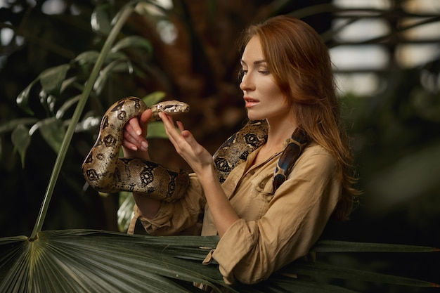 Attractive female zookeeper with python snake in tropical nature