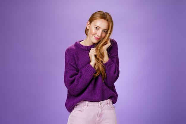 魅力的なフェミニンで恥ずかしがり屋の赤毛の女の子は、カメラのコケティッシュで愚かなポーズを紫色の背景に見ている髪の櫛で遊んでいるカメラでかわいくて優しいようにいちゃつく。
