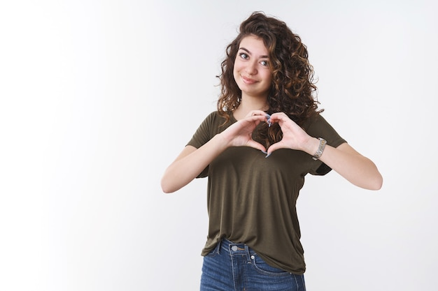 Attractive feminine tender young caucasian woman curly-haired wearing t-shirt show heart shape near chest smiling happily express sympathy love friendship cherish passion, white background