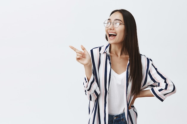 Attraente donna femminile in elegante camicetta e occhiali, ridendo ad alta voce, indicando e guardando nell'angolo in alto a sinistra