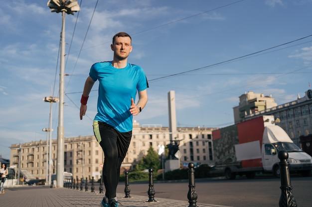 Привлекательный здоровый мужчина, бегущий по городу