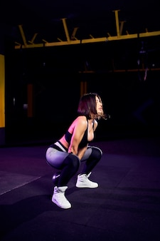 Attractive fit middle age woman athlete performing a kettle-bell swing in cross fit gym