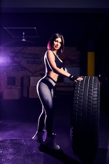 Attractive fit middle age woman athlete posing with a huge tire in the gym. cross fit woman with big tire