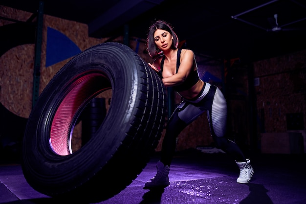 Attractive fit middle age woman athlete working out with a huge tire, turning and flipping in the gym. cross fit woman exercising with big tire