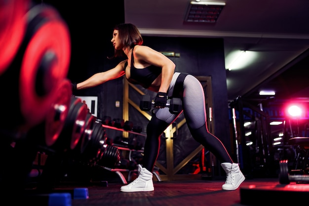 Attractive fit middle age woman in the gym crouches with a barbell. woman training back