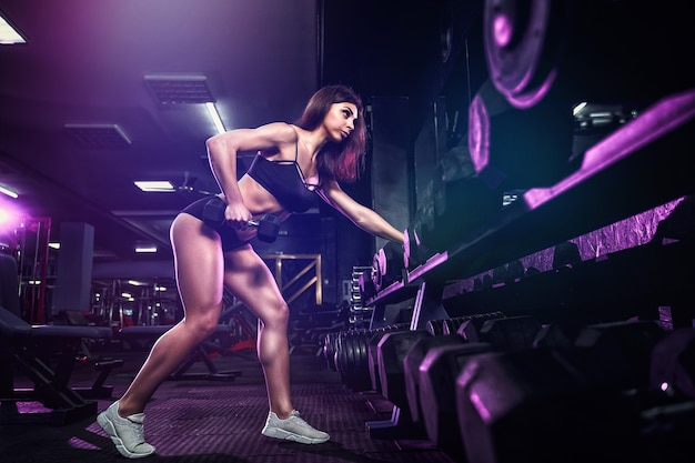 Attractive fit sexy woman in the gym crouches with a barbell. woman training back. colored smoke